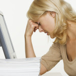 Frustrated Woman at Computer With Stack of Paper