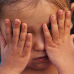young child covering eyes